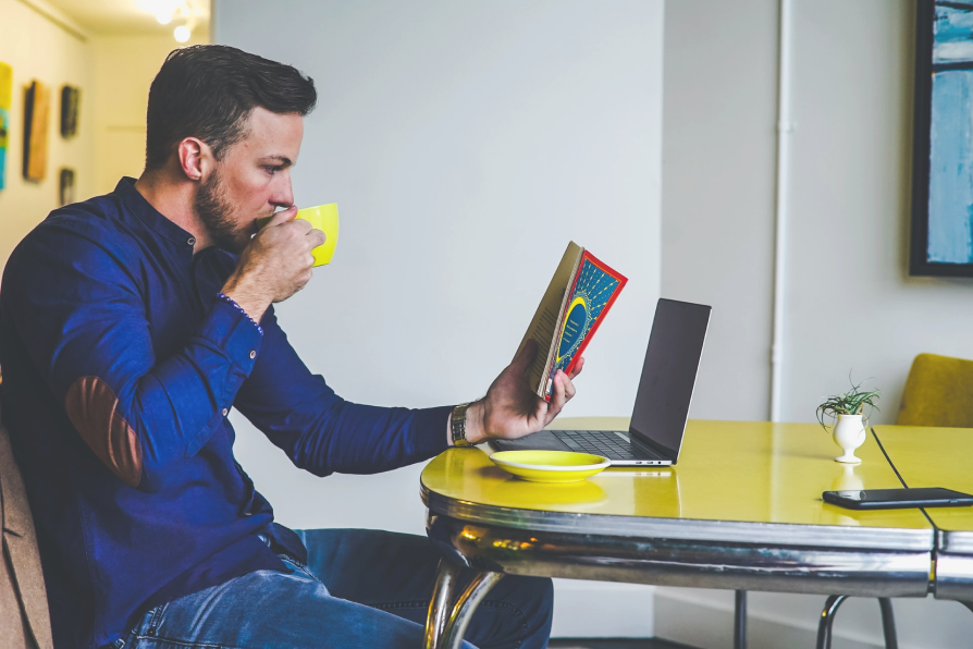 Male sips coffee while reading Atticus guide to estate settlement