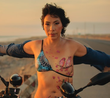 A breast cancer survior sitting confidently astride a motorcycle with a tattoo of birds over her surgery scar