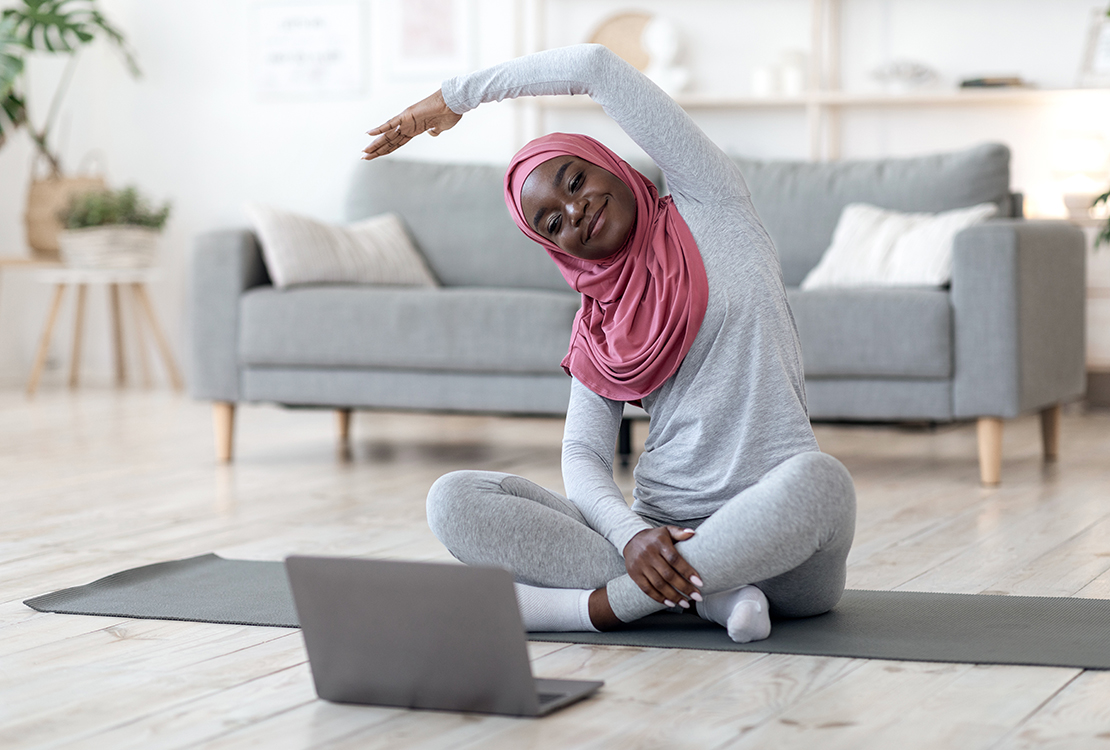 Black woman in hijab doing virtual fitness class