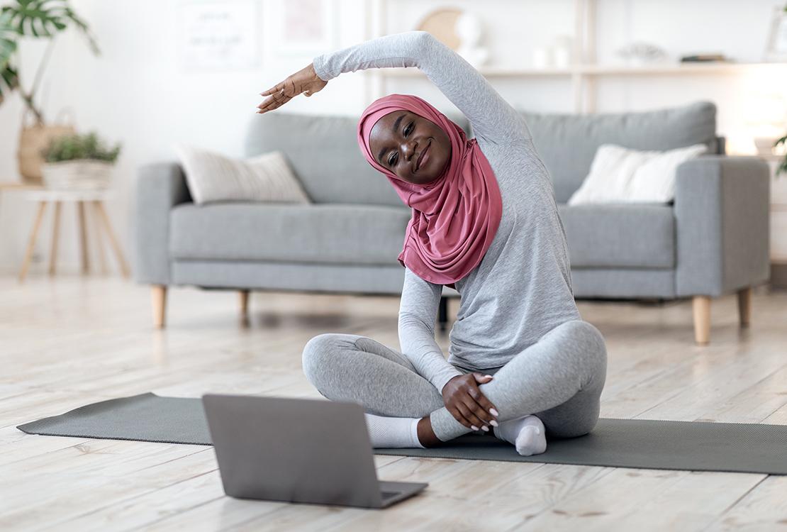 Black woman in hijab doing virtual fitness class