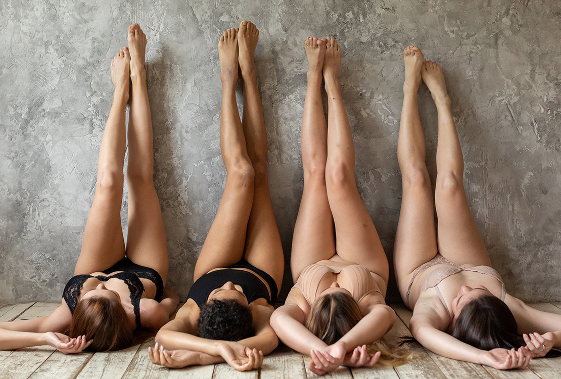 Group of diverse women lying on backs with feet against wall