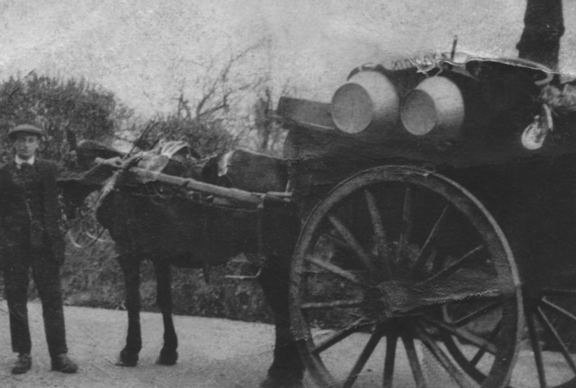 Late 19th century image of a man, horse and cart.