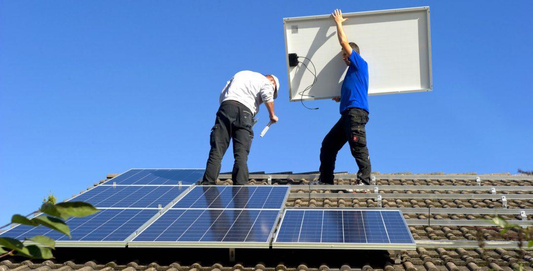 Zwei Männer auf einem Dach, die eine Solaranlage installieren