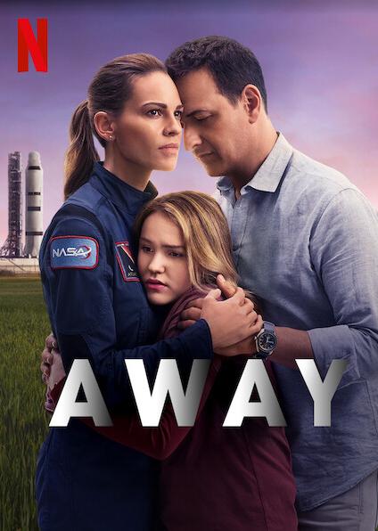 Emma Green in Nasa uniform hugging daughter and husband with rocket behind