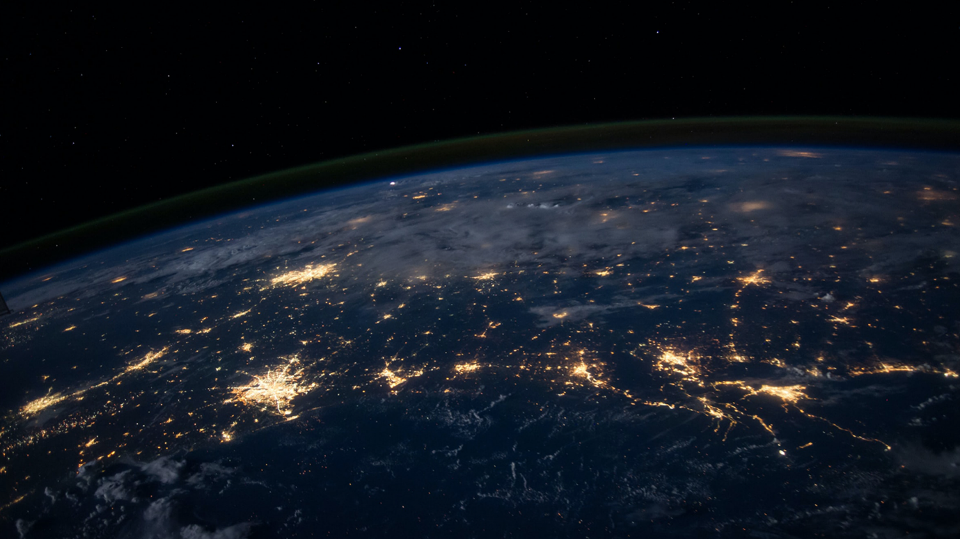 The earth pictured from space with fragments of light connecting the cities