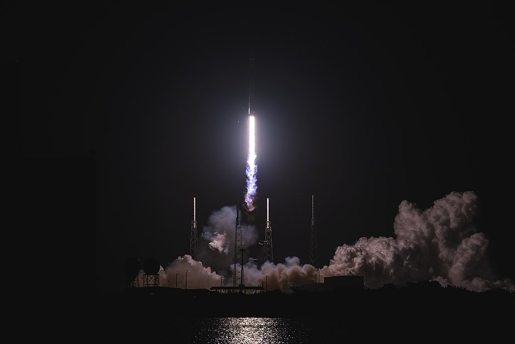 SpaceX Falcon rocket taking off in the dark with a long line of light from the engines following
