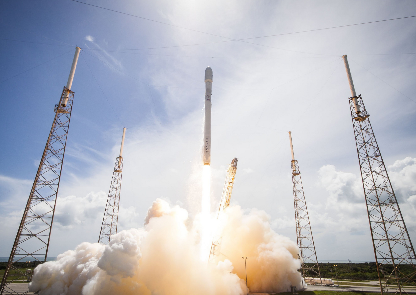 SpaceX rocket launching into bright blue sky with large cloud trailing behind