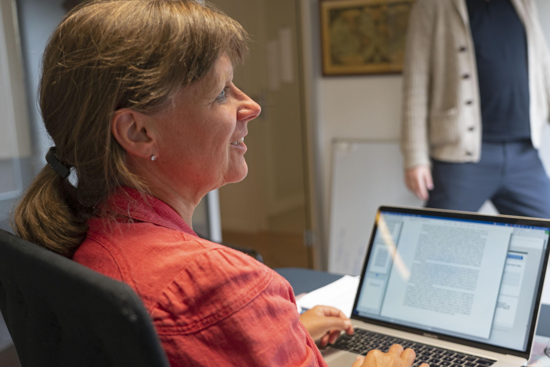 Kristin Omholt-Jensen sitting at her desk.