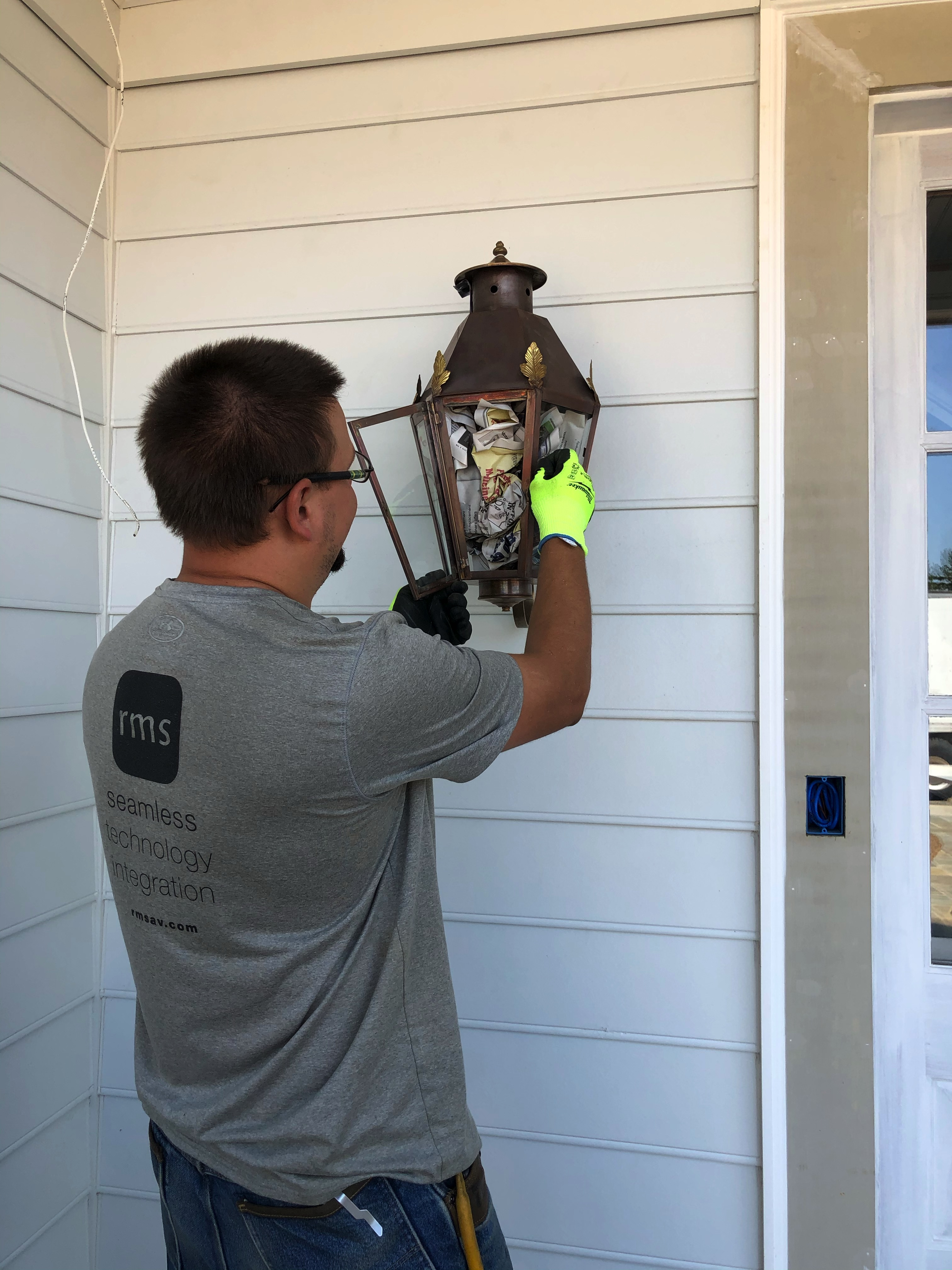 Electrician working hard on exterior light