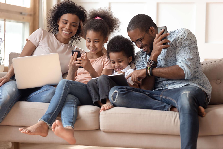 Family of 4 enjoying technology