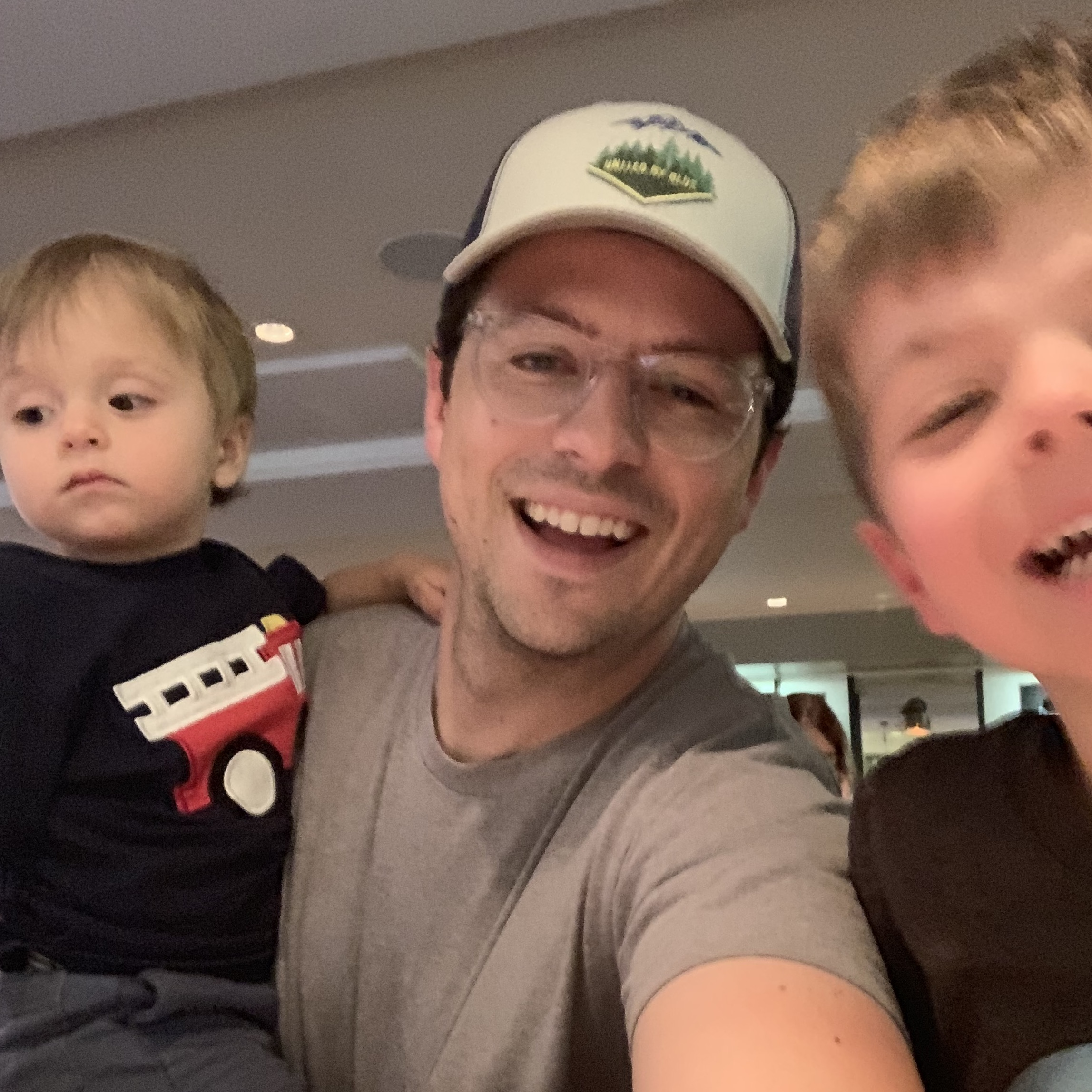 Bryan smiling indoors with two of his children