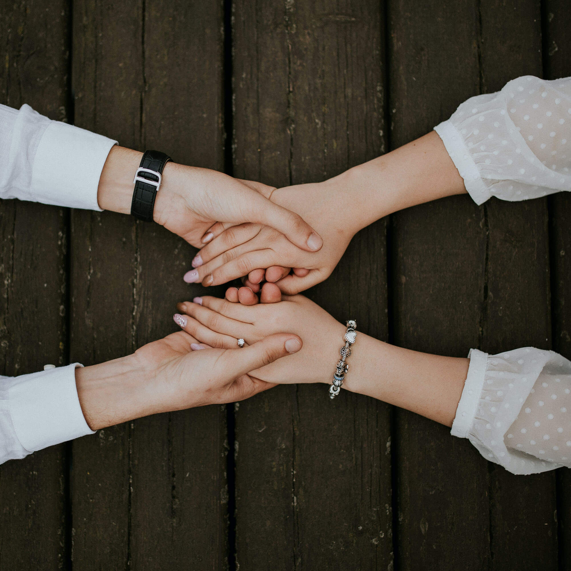 Two pairs of holding hands on top of a wooden table