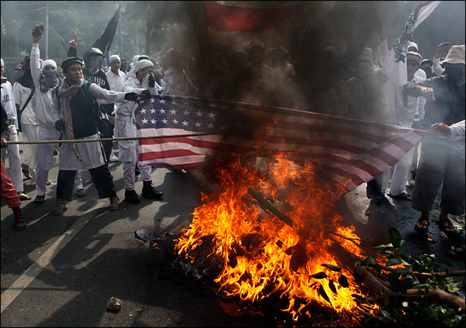 "Muslim protesters burn a U.S. flag during a protest against the American-made film ""Innocence of Muslims,"" outside the U.S. Embassy in Jakarta, Indonesia, Monday, Sept. 17, 2012. (AP Photo/Dita Alangkara)"