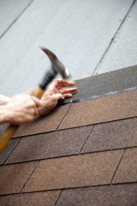 roofer hammering nails in roof