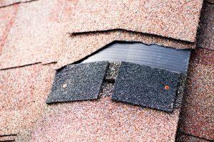 Roof with torn missing asphalt shingle