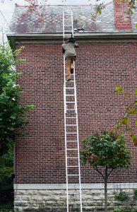 Man climbing ladder to maintain gutters