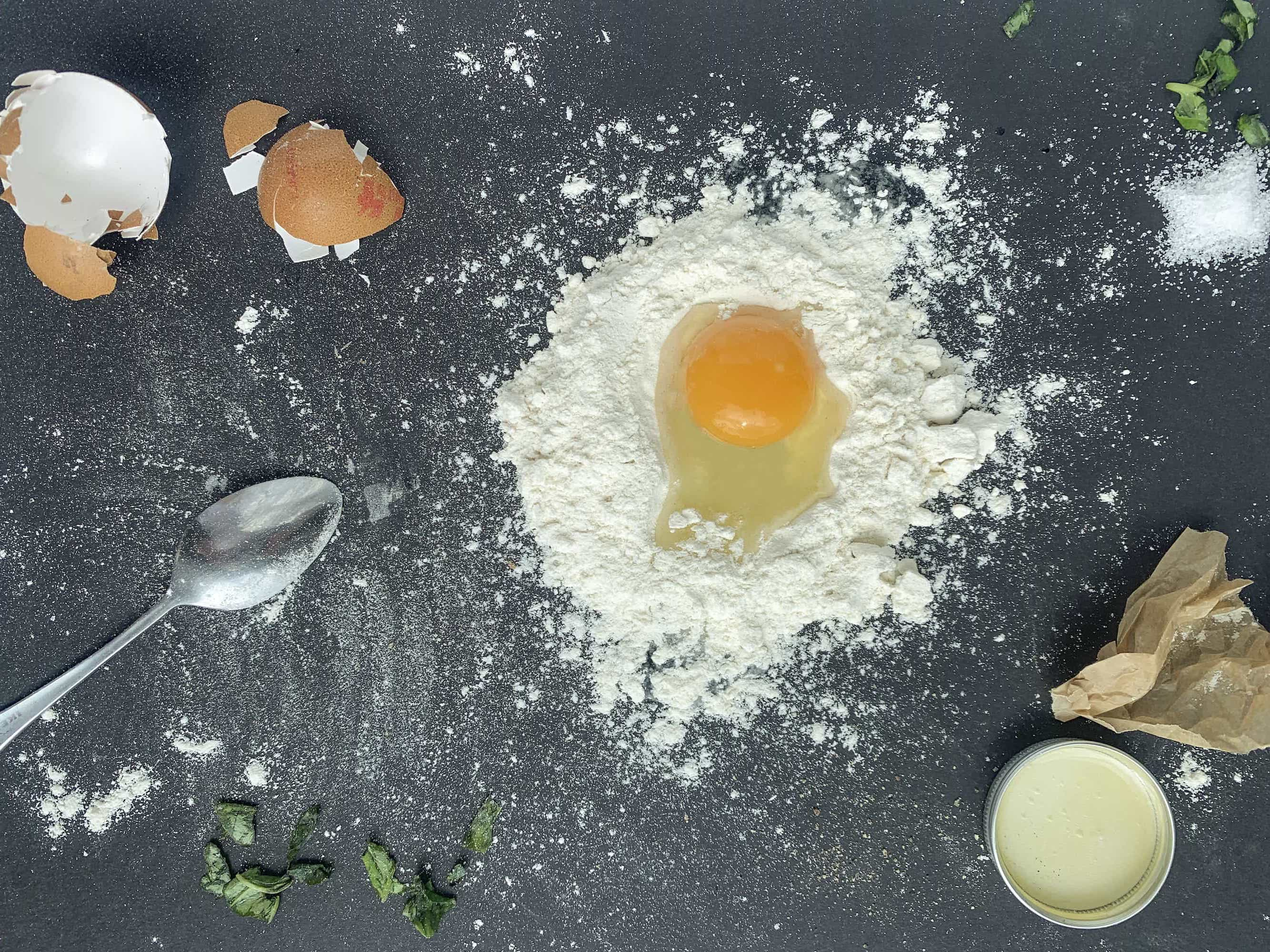 Table-with-cracked-egg-flour-and-spoon