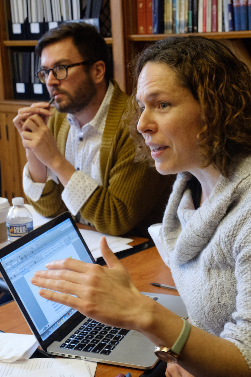 Two early-career faculty members discuss research in a room with bookshelves