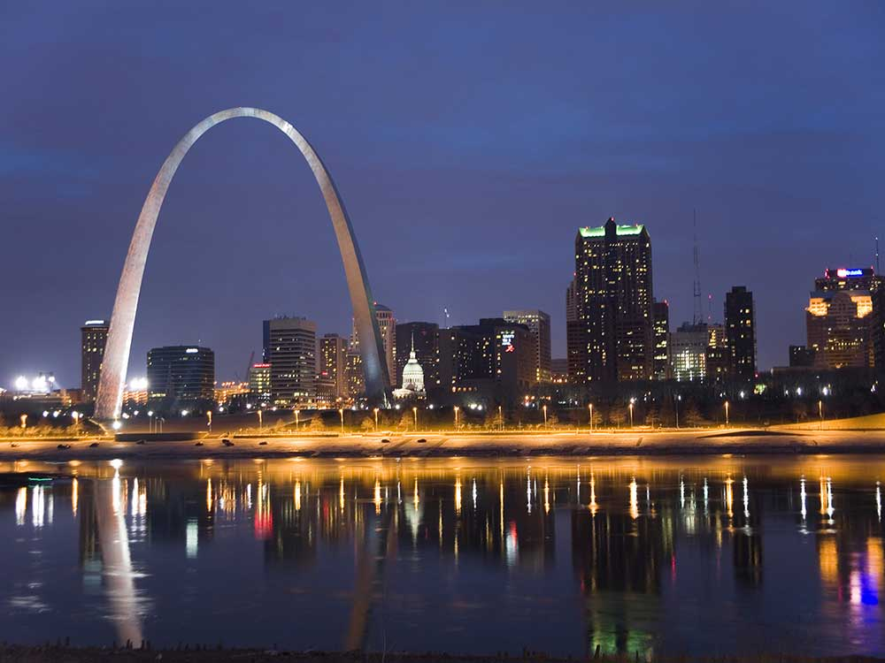 Saint Louis Arch and city at night with Mississippi river in foreground.