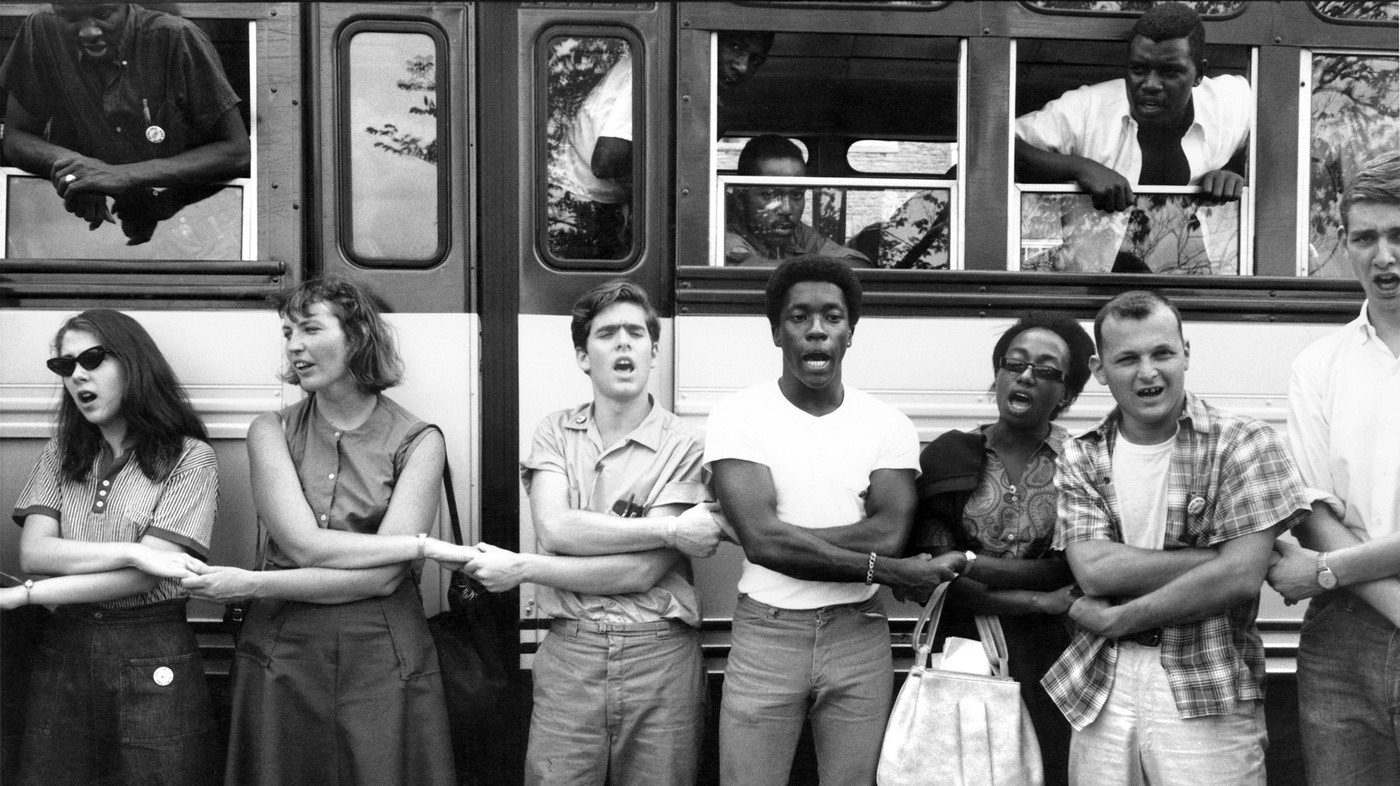 A black and white photo of black and white students forming holding hands in front of a bus
