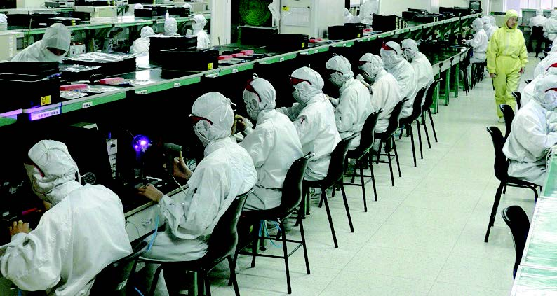 A line of workers sit at desks working on electronics