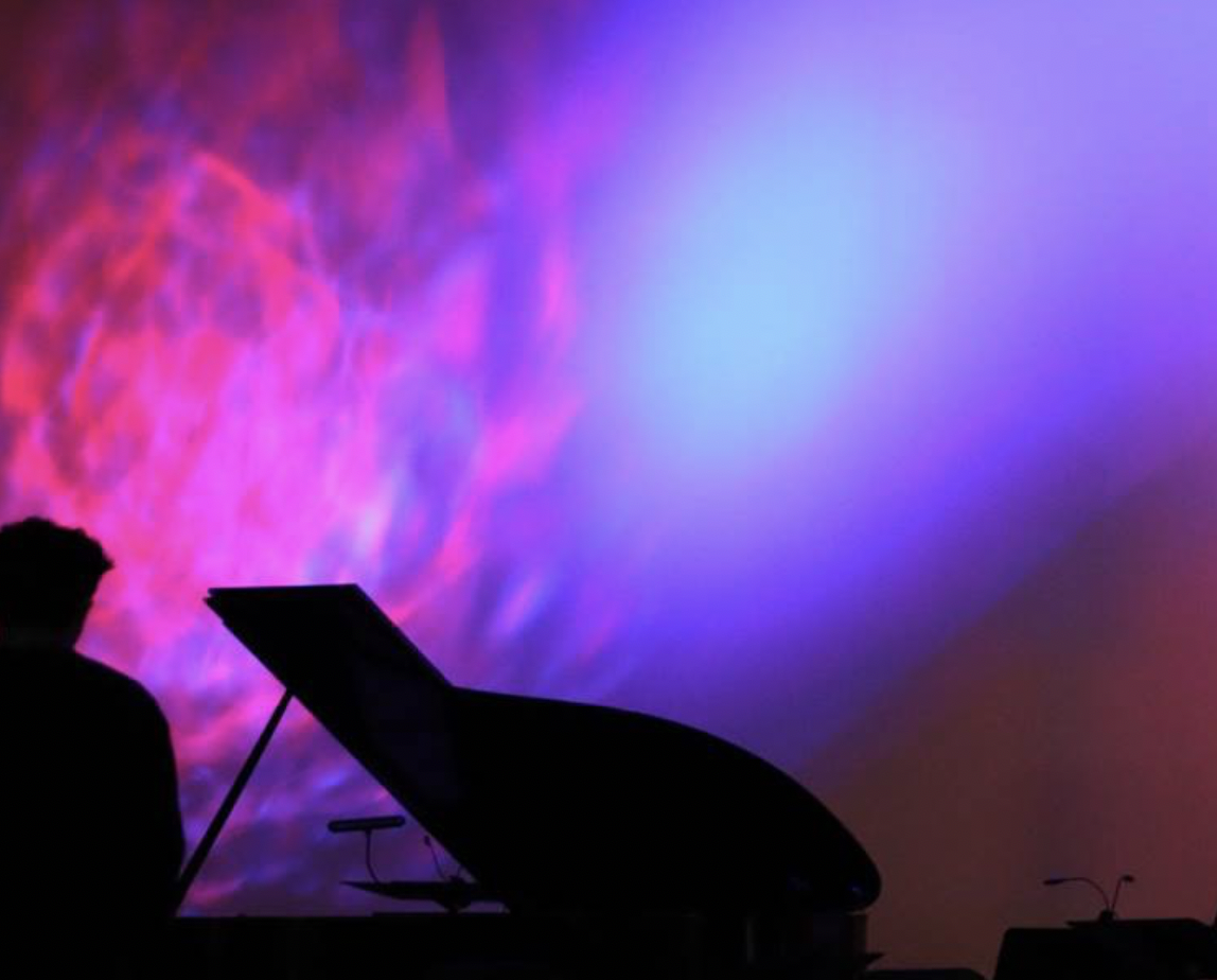 silhouette of person at piano against a neon backdrop