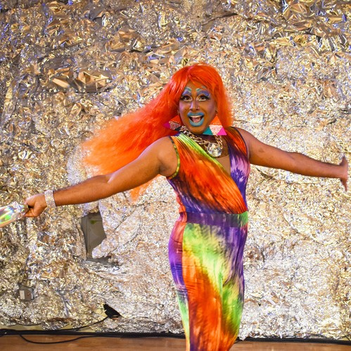 Drag queen LaWhore Vagistan twirls in front of a glittery backdrop in a rainbow jumpsuit
