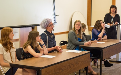 six students discuss their work while a professor moderates the conversation