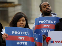 Protesters hold protect my vote signs