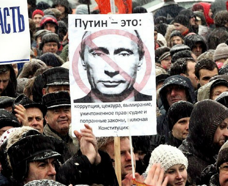 People holding up sign of Putin with a slash through it