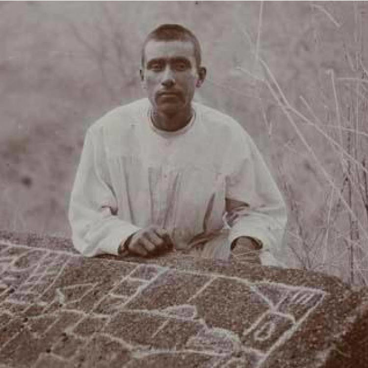 man in a tunic siting in front of a stone tablet