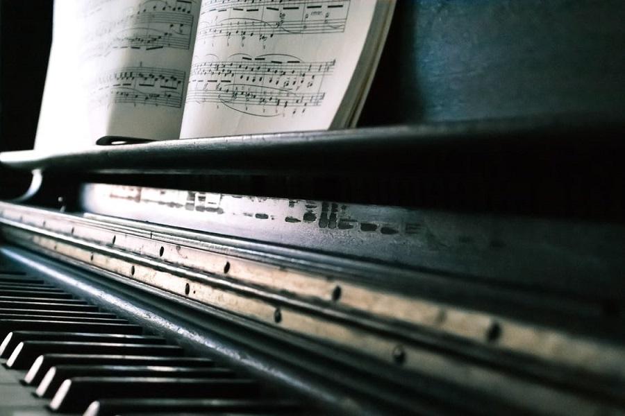 Up close of piano keys and sheet music.