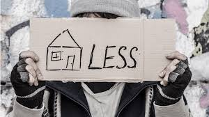 Person holding a cardboard sign that say homeless in front of their face