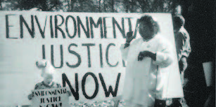 """A woman speaking in front of a large sign that says """"Enviornmental Justice Now"""""""