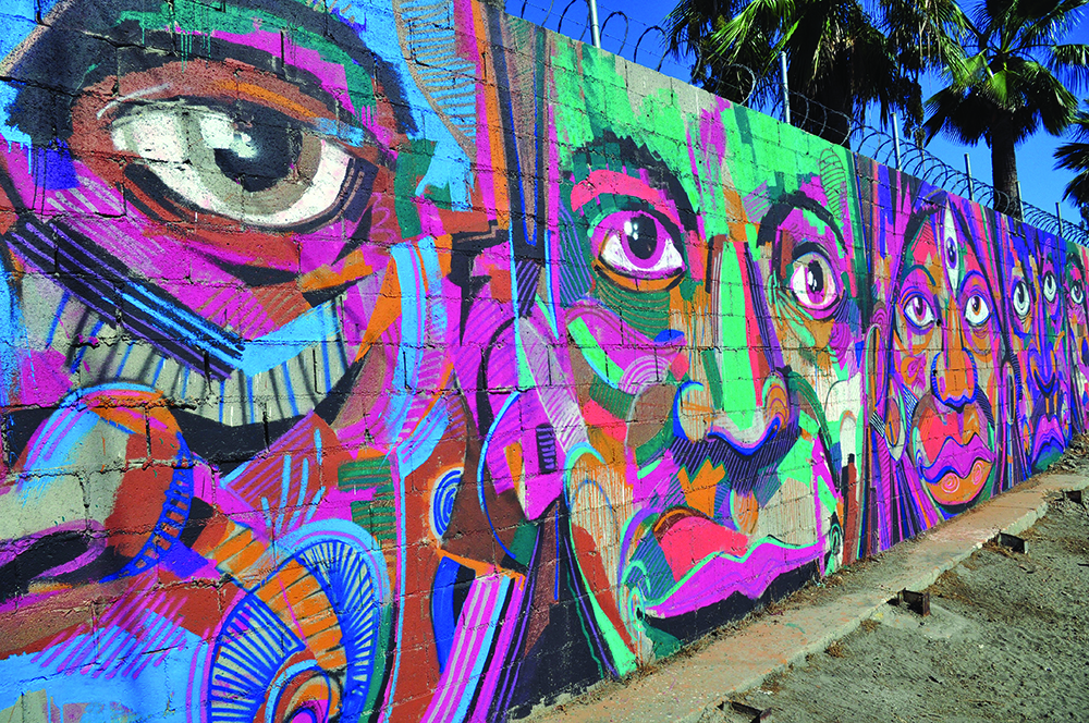 graffiti of abstractly multicolored faces along a border wall