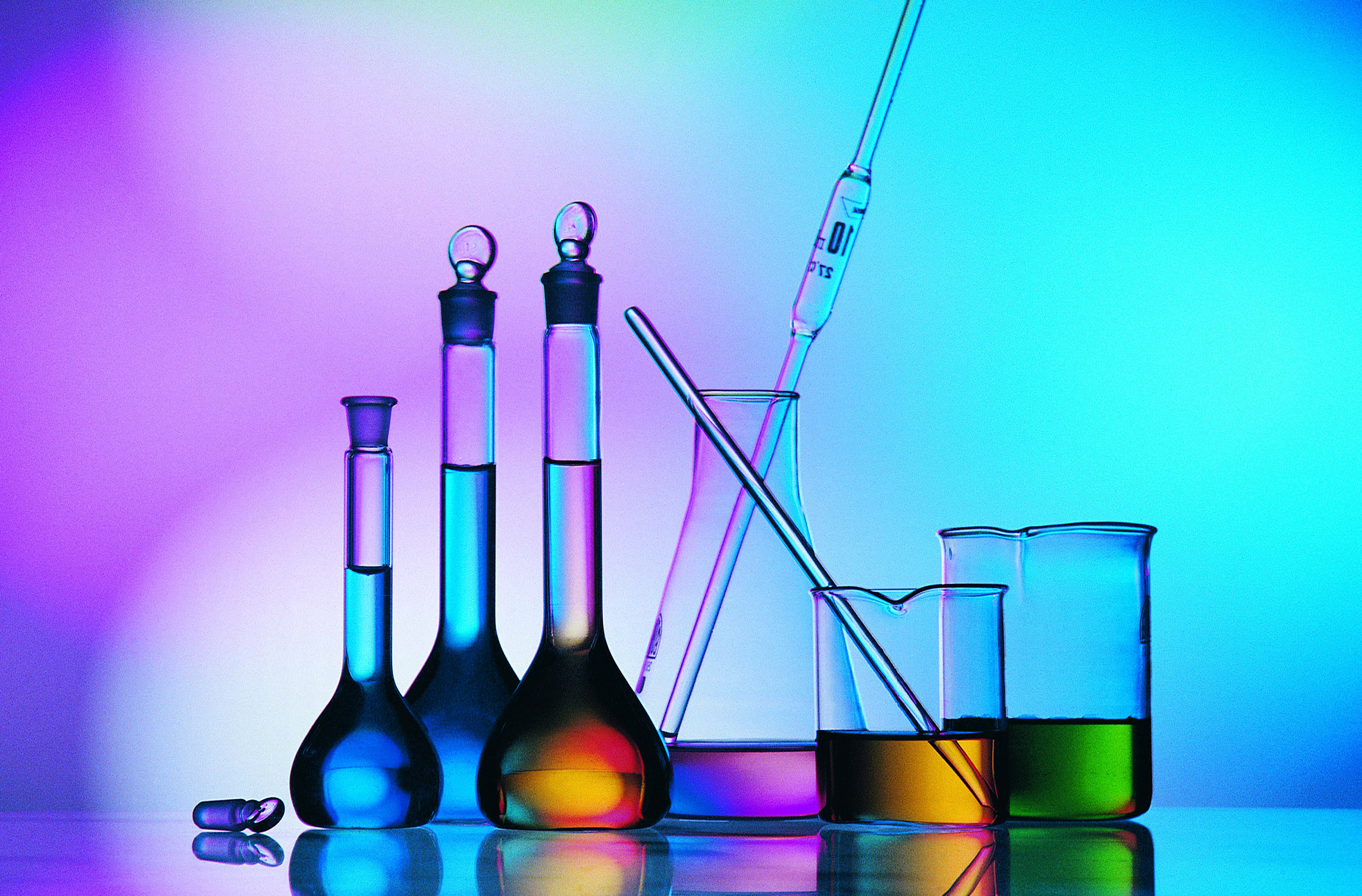 beakers and test tubes on a neon colored background