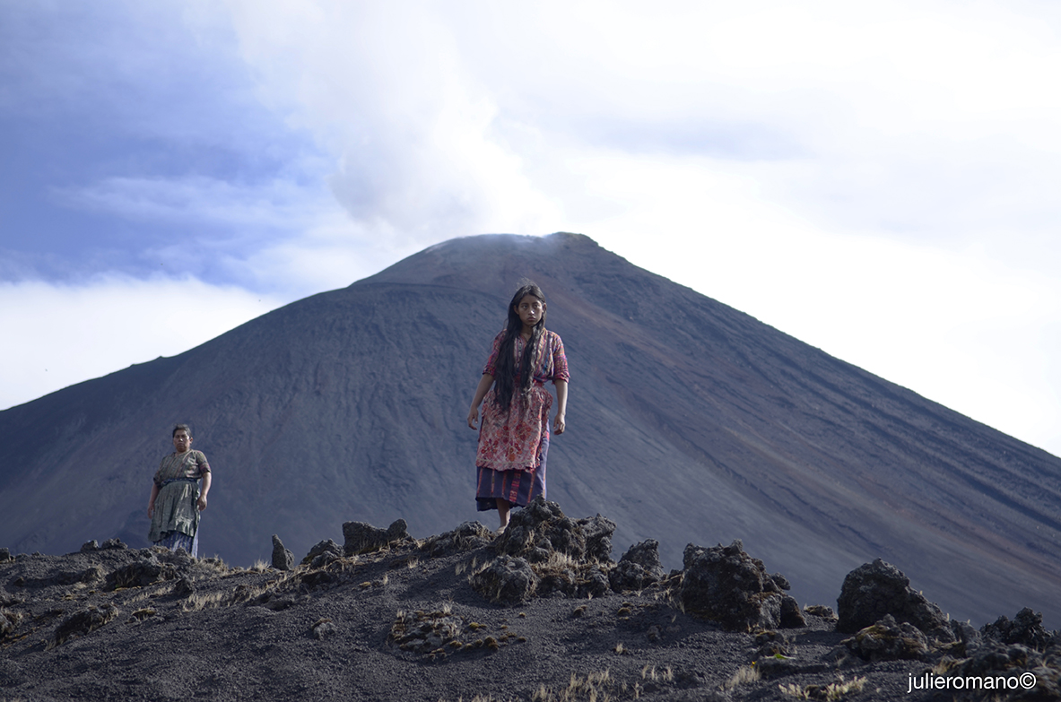 Two individuals stand in front of a volcano