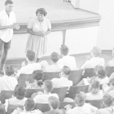 Black and white photo of two presenters in front of an audience