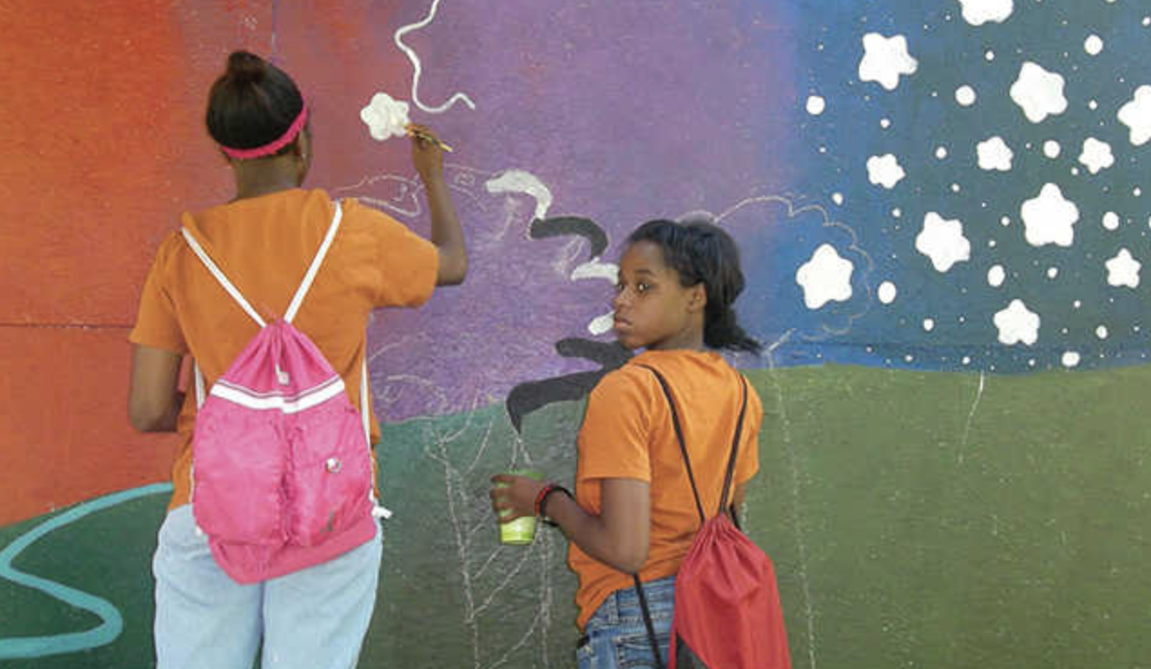 Two young black girls painting a mural on a wall