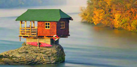 A small toy house sits on a rock in a river