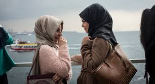 Two women wearing veils have a conversation