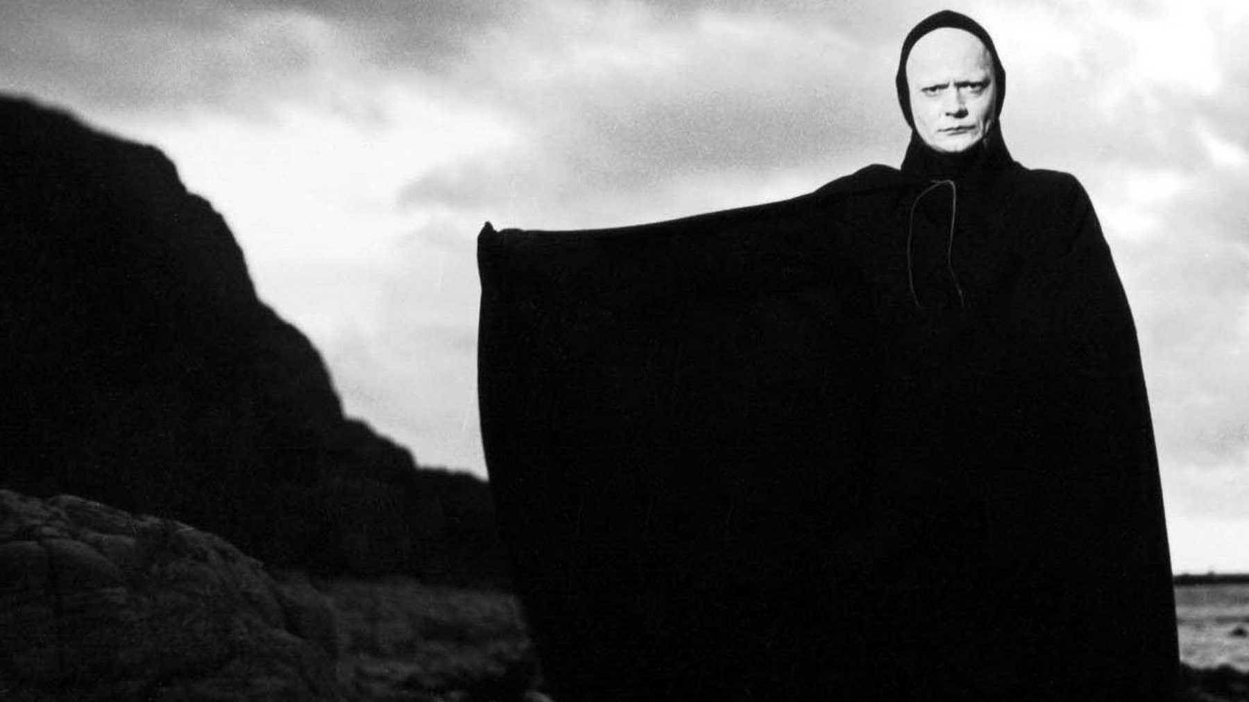 man in a black cape with a white face in front of rocky beach