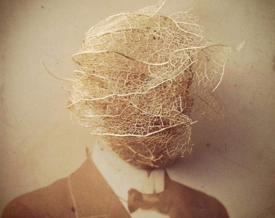 Old picture of a man with head covers by a thin gossamer like fabric ball