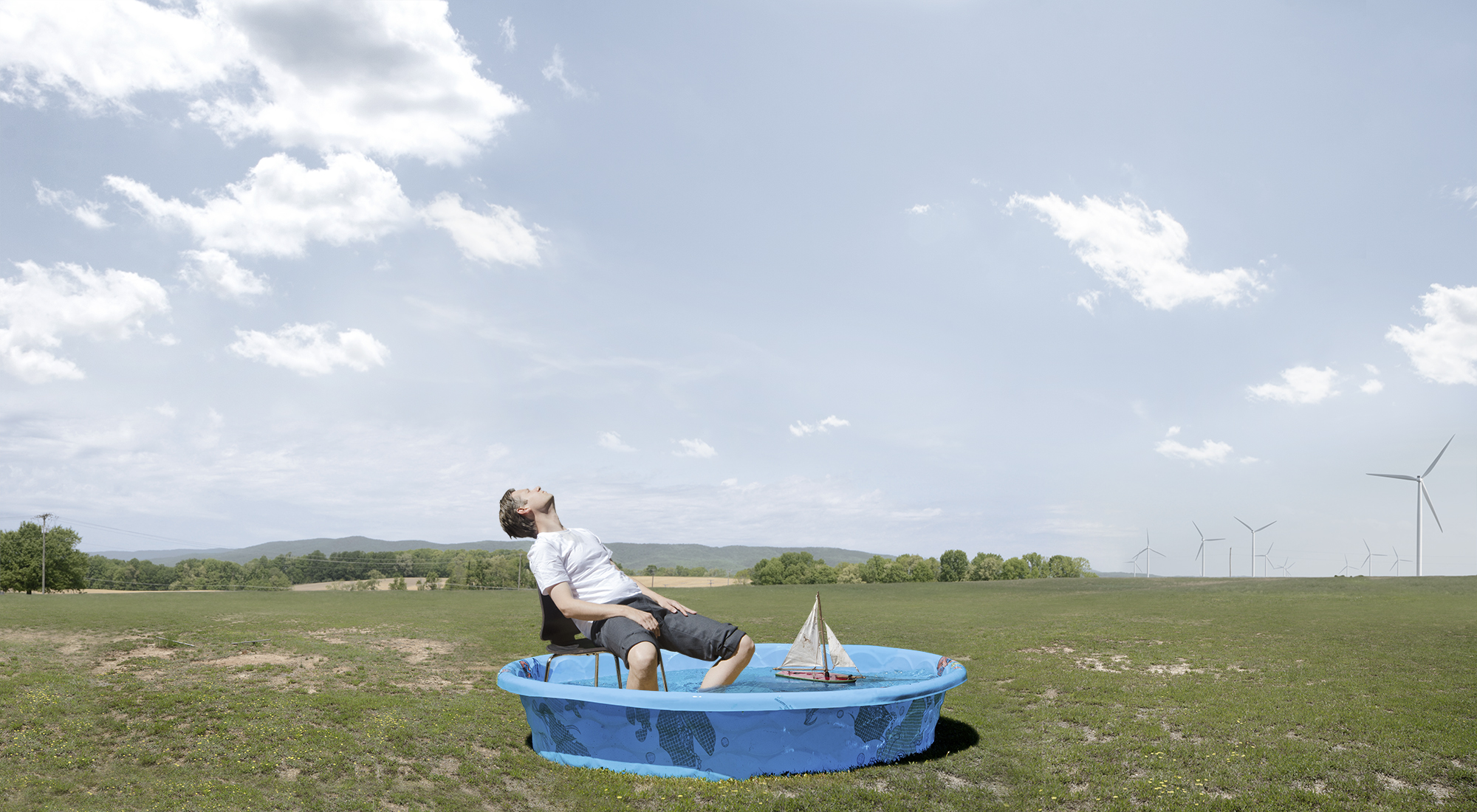 Man sitting in chair with feet in kiddie pool with electric windmills in the background