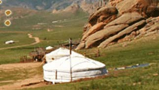 A rocky grassland feauring white tents