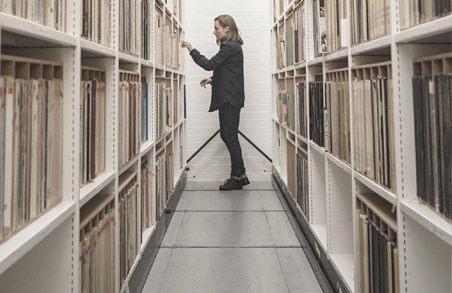 research perusing the shelves of an archive