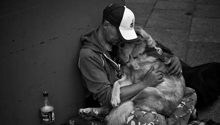 A homeless man sitting against a wall holding a golden retriever