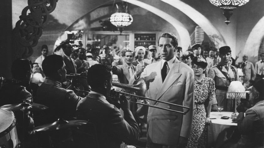 black and white image of a man dressed in a white suit standing inside of a small jazz club