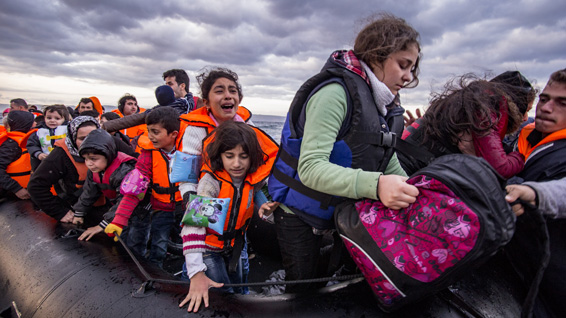 Refugees, in life jackets, packed together on a large raft