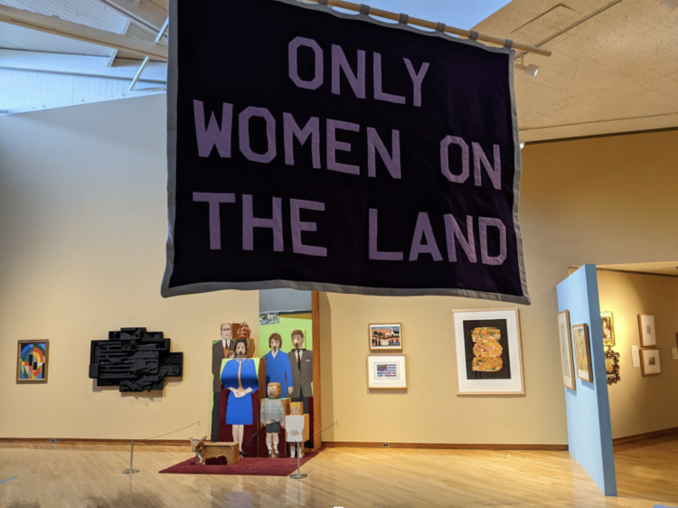 "Sign reading ""only women own the land"""